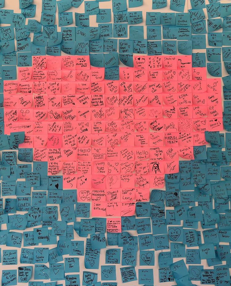 Pink and blue post-it notes arranged into a heart pattern