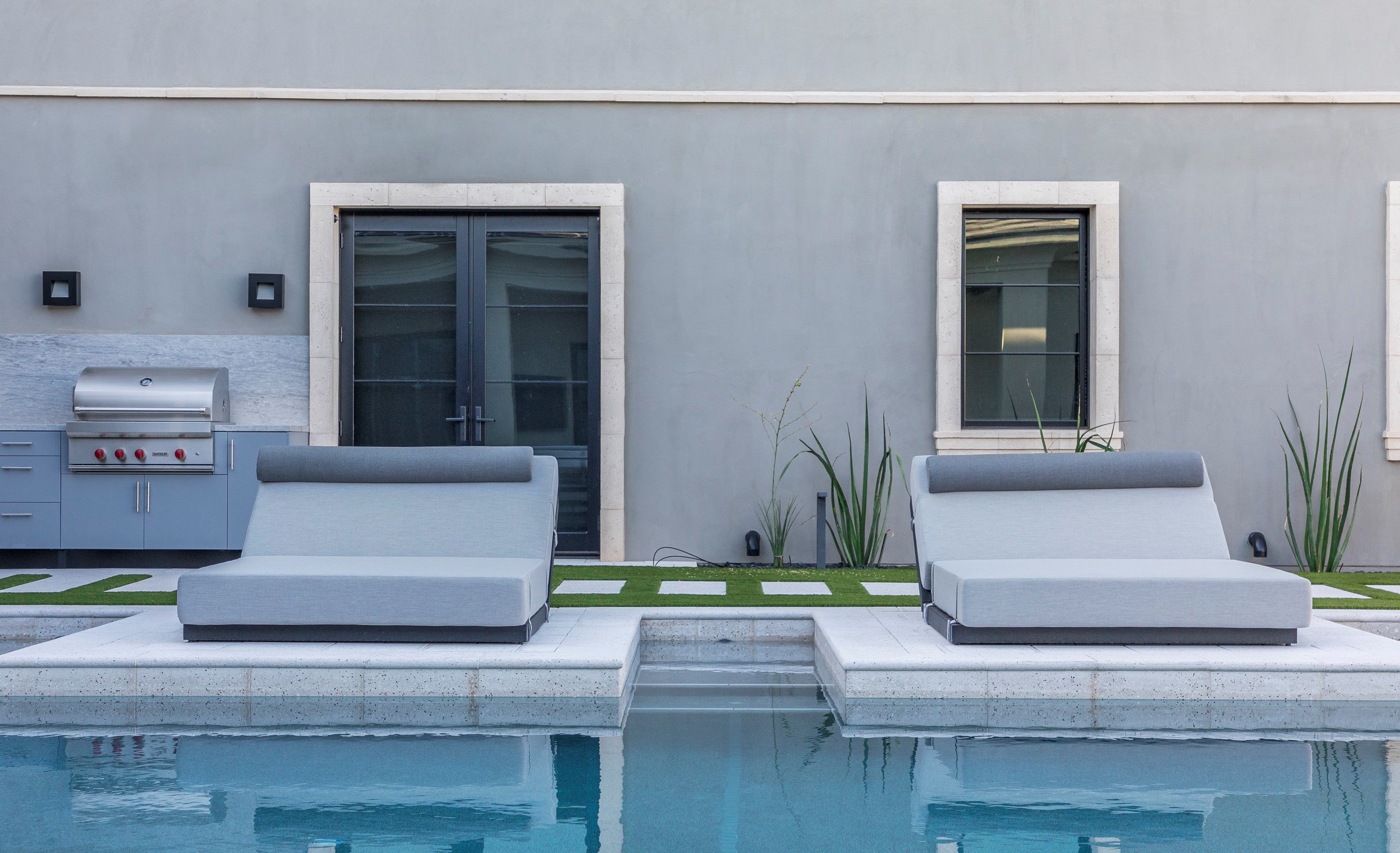 Cushioned lounge chairs next to a pool